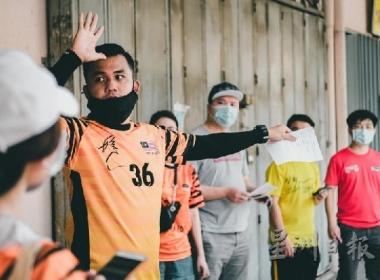 在派送物资前,和平足球队队员及马来西亚基督教福音宣教会会员聆听曾贵仁(左二)进行的简报。